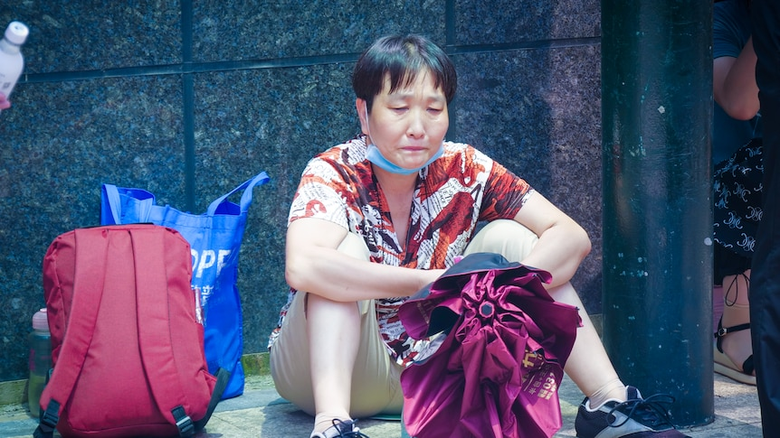 A Chinese woman sitting on the floor outside a building, crying